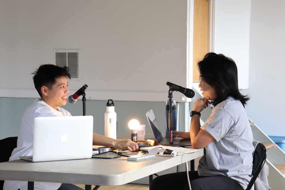 So Mak and Bex Kwan sit across from each other at a gray table, a single light bulb glowing between them as they speak into microphones.