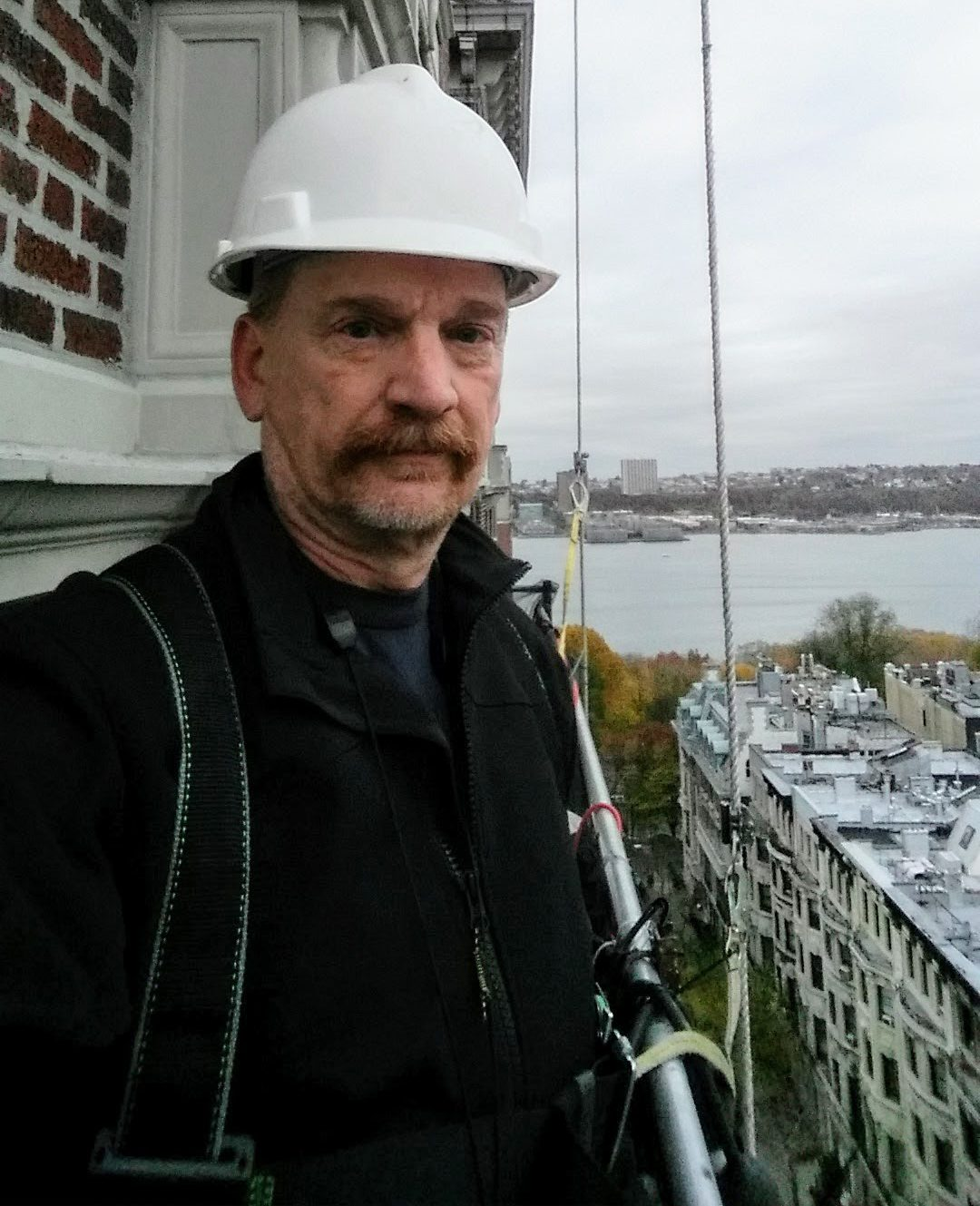 Ron Mitkowski stands on a scaffold suspended from a building.